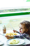 Little baby girl sitting in the restaurant or cafe and eating food. Stock Images