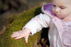Little baby girl sitting in a spring forest Royalty Free Stock Image