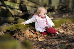 Little baby girl sitting in a spring forest Royalty Free Stock Photo