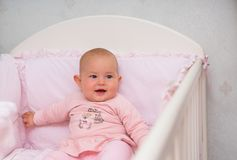 Little baby girl sitting in a pink crib. royalty free stock photography