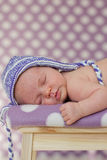 Little baby girl, sleeping on a chair. With hat Stock Photo