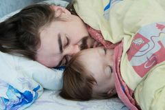 Little baby girl sleeping with dad in the morning. Happy parent. Father lying on bed. Happy family. stock photography