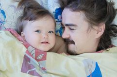 Little baby girl sleeping with dad in the morning. Happy parent. Happy family. royalty free stock images