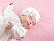 Little baby girl sleeping dressed in white suit Stock Photography