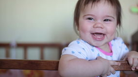 Little baby girl standing on the bed and laughing stock footage