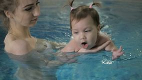 Little baby girl swimming. Learning infant child to swim.  stock video