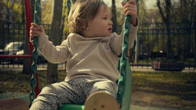 Little baby girl on a swing Stock Images