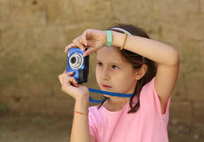 Little girl takes a photo with the digital camera Stock Photos