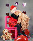 Little baby girl toddler sitting on small pink chair with bear toy in studio Royalty Free Stock Image