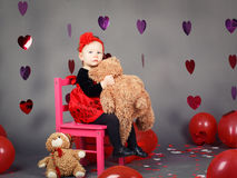 Little baby girl toddler sitting on small pink chair with bear toy in studio Royalty Free Stock Photography