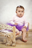 Little baby girl in tutu skirt sitting on the small bed Royalty Free Stock Photos