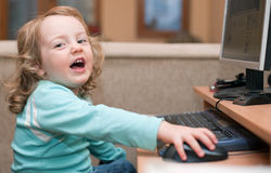 Little baby girl using a desktop computer, smiling Stock Photos