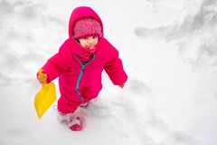 Little baby girl view play snow wearpink child ski suit winter. Little baby girl view from above play with snow wear pink child ski suit in winter stock photography