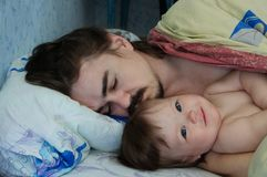 Little baby girl wake up in the morning. Parent tired sleeping. Father lying on bed stock photography
