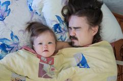 Little baby girl sleeping with dad in the morning. Happy parent. Happy family. stock images