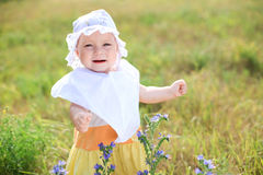 Little baby girl walking by green field Royalty Free Stock Photo