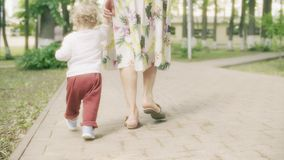 Little baby girl walks holding her mom`s hand in the park on a summer day stock images