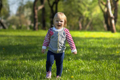 Little baby girl walks in the park Stock Images