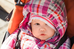 Little baby girl in warm outwear seats in pram Royalty Free Stock Photography
