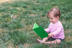 Little baby girl watching a book with pictures Stock Photos