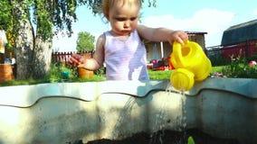 Little baby girl wattering plants stock video footage