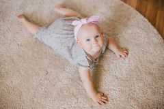 Little baby girl wearing bow crawling on a floor. And smiling royalty free stock images