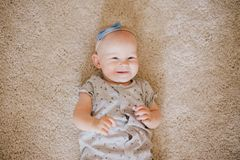 Little baby girl wearing bow crawling on a floor. And smiling royalty free stock image