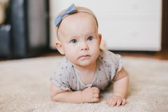 Little baby girl wearing bow crawling on a floor. And smiling royalty free stock photography