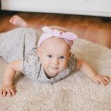 Little baby girl wearing bow crawling on a floor. And smiling royalty free stock photo