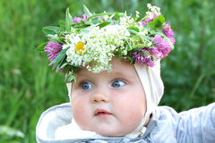 Little baby girl wearing flowers and herbs crown in solstice nig Stock Image