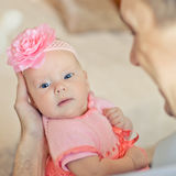 Little baby girl wearing pink knitting dress. And rose adortment/ Father holding daughter Royalty Free Stock Photography
