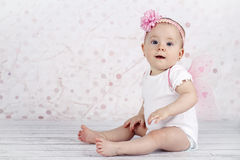 Little baby girl wearing wings catching bubbles Stock Photos