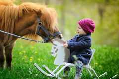 Little baby girl on wooden rocking horse and pony. In spring park Stock Photo