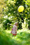 Little baby girl with a yellow balloon. In the forest Stock Photos