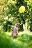 Little baby girl with a yellow balloon Stock Photos