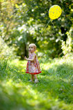 Little baby girl with a yellow balloon. In a forest Royalty Free Stock Photos