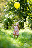 Little baby girl with a yellow balloon. In a forest Stock Images