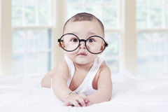 Little baby with glasses lying on bed Stock Photography