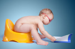 Little baby with glasses sitting on the toilet Royalty Free Stock Images