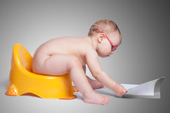 Little baby with glasses sitting on the toilet Stock Photography