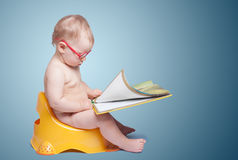 Little baby with glasses sitting on the toilet Stock Image