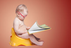 Little baby with glasses sitting on the toilet. And reading a book, on color background royalty free stock photography