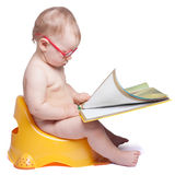 Little baby with glasses sitting on the toilet. And reading a book. on white background stock images