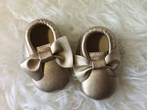 Little baby gold shoe on white fluffy background royalty free stock photos