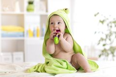 Little baby in green towel biting toy after bath. Infant boy with teether. Child health care. Little baby boy in green towel biting toy after bath. Infant boy Stock Photography