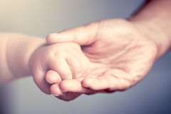 Little baby hand holding his mother finger Stock Images