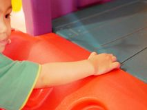 Little baby hand holding tightly on a plastic panel while climbing stairs stock image