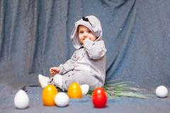 Little baby in hare jumpsuit and easter eggs. Baby in rabbit costume and with Easter eggs royalty free stock photo