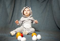 Little baby in hare jumpsuit and easter eggs stock images