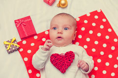 Little baby with heart shape toy Stock Images
